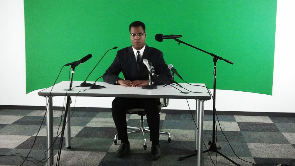 sam-at-desk-with-green-screen